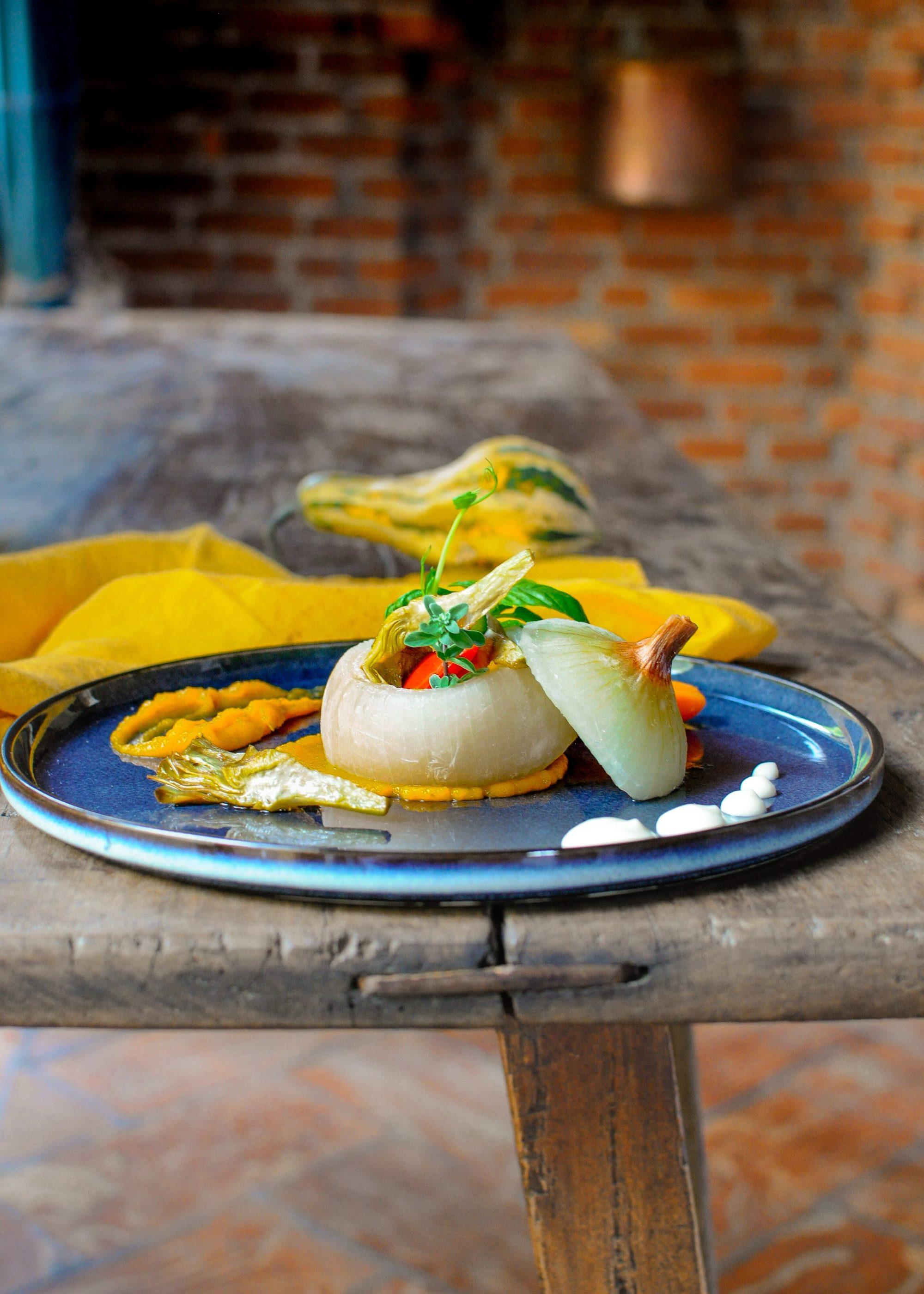 Cipolla dolce ripiena di zucca e verdure di stagione con fonduta di tomino di capra di Casale Roccolo